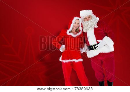 Santa and Mrs Claus smiling at camera against red snowflake background