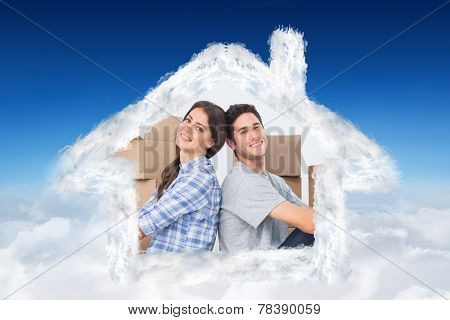 Happy couple sitting back-to-back against blue sky over clouds
