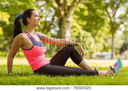 Cheerful fit brunette day dreaming on the grass in the park