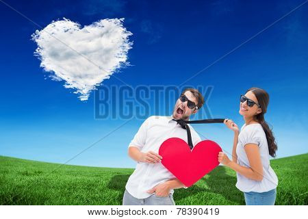 Brunette pulling her boyfriend by the tie holding heart against cloud heart