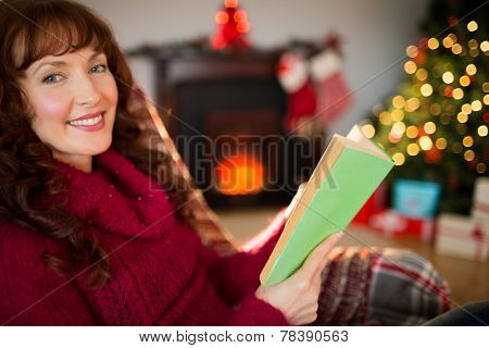 Smiling red hair reading on the couch at christmas at home in the living room