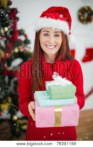 Festive redhead holding christmas gifts against snow falling