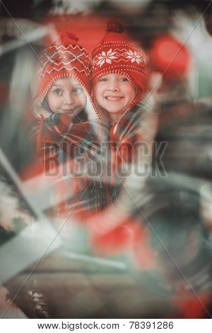 Festive little girls under a blanket against instant photos on wooden floor