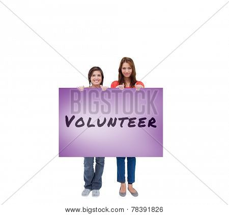 Smiling young women proudly holding a blank poster against purple card