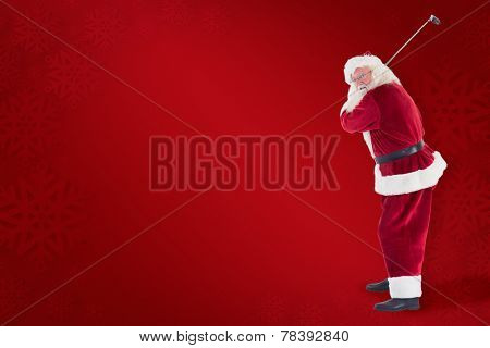 Santa Claus swings his golf club against red background