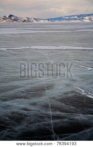 Winter baikal. Ice field and mountain on background