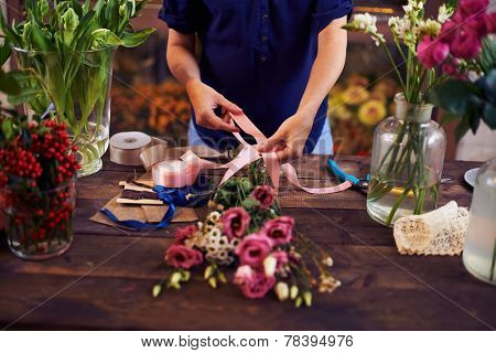 Flowers on wooden table and in glassware and hands of decorator going to tie them up with pink ribbon