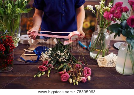 Roses on wooden table and in glassware and hands of decorator with pink ribbon