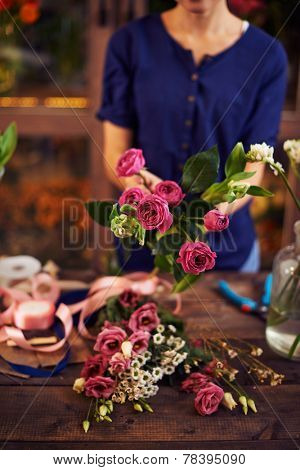 Female decorator or vendor holding several fresh pink roses