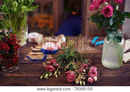 Roses on wooden table and in glassware in studio of design