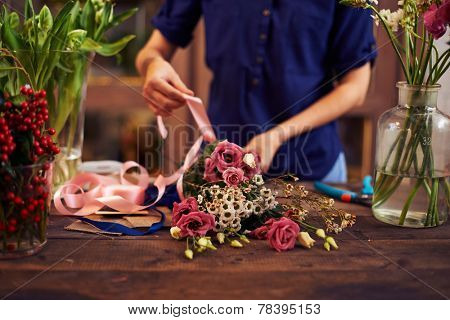 Female decorator tying flowers up with pink ribbon