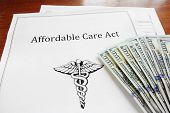picture of insurance-policy  - Affordable Care Act insurance papers with cash - JPG