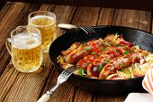 pic of sausage  - Sausages fried in cast iron skillet with two beer mugs on wooden background - JPG