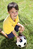 Постер, плакат: Молодой мальчик вне игры с футбол или футбол мяч