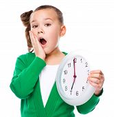 stock photo of hush  - Cute girl is holding big clock and showing hush gesture isolated over white - JPG