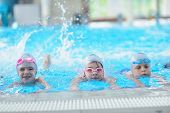 picture of swimming  - group of happy kids children   at swimming pool class  learning to swim - JPG