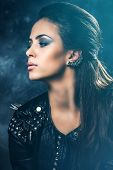 stock photo of stud  - young beautiful woman portrait in black leather jacket with studs - JPG