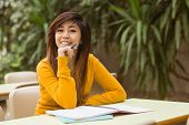 stock photo of canteen  - Portrait of female college student doing homework in outdoor canteen - JPG