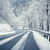 stock photo of slippery-roads  - Winter country road leading through a mountain landscape - JPG