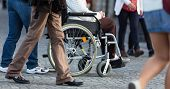 pic of street-walker  - Close up of  woman on a wheelchair with a helper during walk in the busy street - JPG