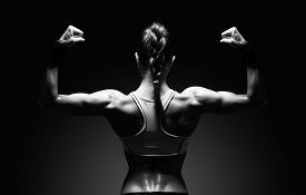 foto of shoulder muscle  - Athletic young woman showing muscles of the back and hands on a isolated black background with clipping path - JPG