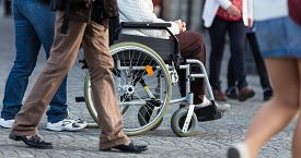 picture of street-walker  - Close up of  woman on a wheelchair with a helper during walk in the busy street - JPG