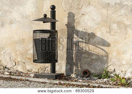 Black trash can near the wall.