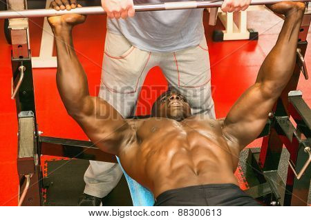 Hunky muscular black bodybuilder working out in gym on bench