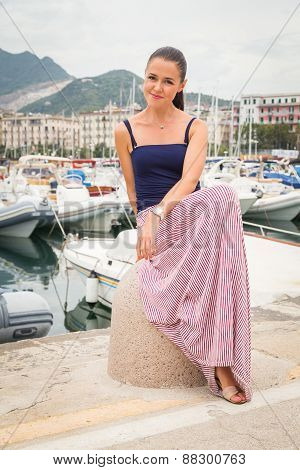 Beautiful girl, brunette on the pier. Yachts, boats, fishing boats in the background