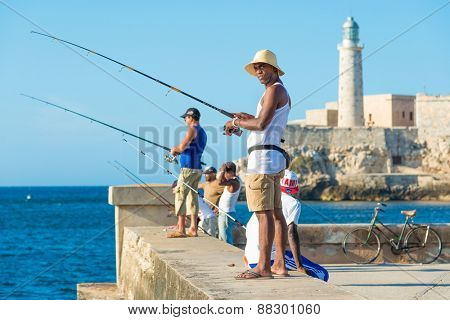 HAVANA, CUBA - APRIL 14,2015 : Cubans fishing in front of the famous El Morro castle, a worldwide known cuban landmark