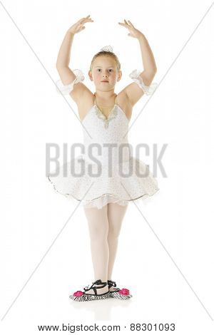 A young elementary ballerina in her white dance costume standing gracefully in third position.  On a white background.