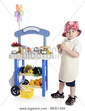A adorable preschooler looking sad as he stands by his his fruit stand.  On a white background.