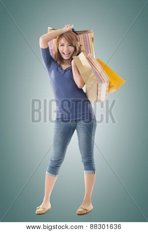Cheerful shopping woman of Asian holding bags, isolated.