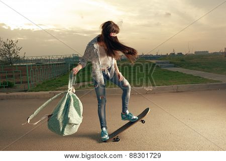 speeding skateboarding woman at city with backpack in her hands