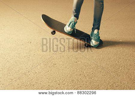 Female on skateboard legs and a lot of copyspace on asphalt