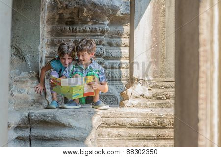 two young children looking at tourist map in Angkor wat, cambodia