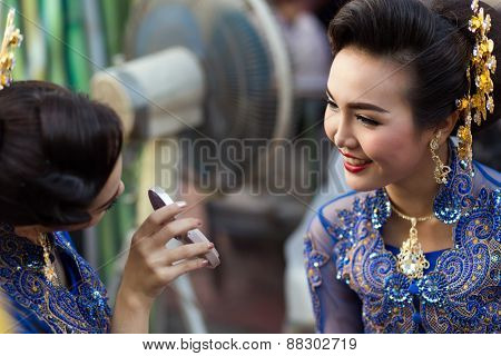 BANGKOK, THAILAND, February 17, 2015: A Thai lady dancer is checking up her makeup before the show at the new Krung Kasem floating market in the Thewet district of Bangkok, Thailand