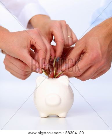 Putting coin into the piggy bank .