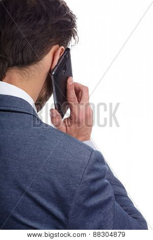 Young businessman talking on mobile isolated on white background. back view