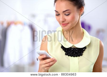 Pretty fashion designer working in office using mobile phone.