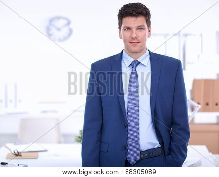 Business man or manager standing against his desk at the office isolated