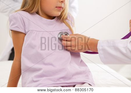Female doctor examining child with stethoscope at surgery .