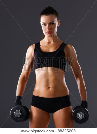 Athletic woman pumping up muscules with dumbbells .