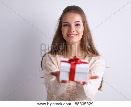 Young woman happy smile hold gift box in hands, isolated over gray background .