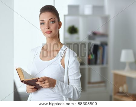 Attractive businesswoman standing near wall in office with book .