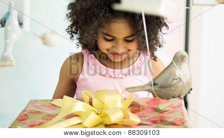 Cute mulatto girl holding a gift