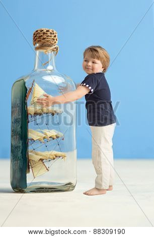 Little boy next to a ship in a bottle