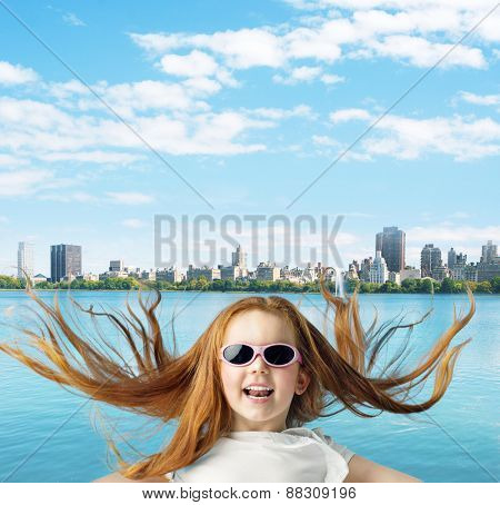 Cute little ginger hair girl over modern cityscape