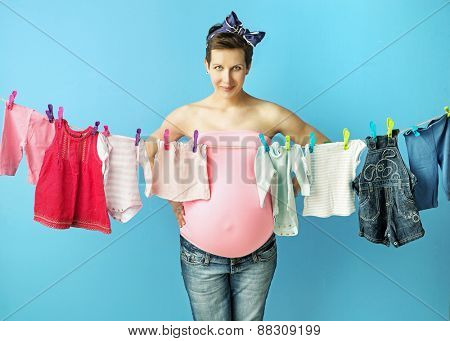 Pregnant woman posing next to baby clothes