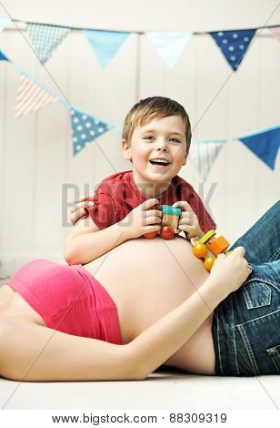 Happy childplaying next to belly of pregnant woman